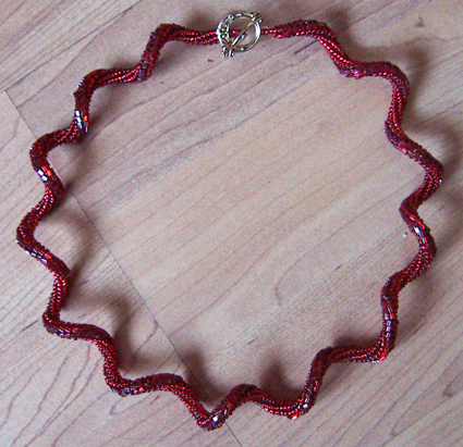 A picture of a red herringbone spiral necklace