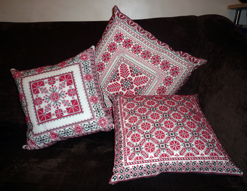 Picture of three cushions embroidered in red and black